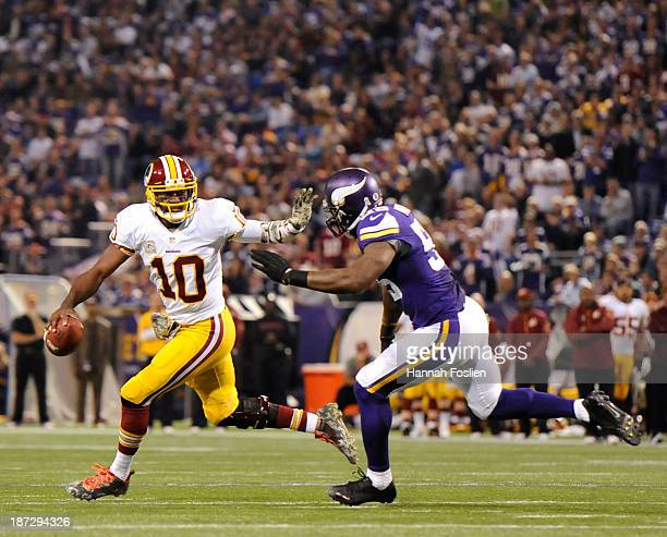 Robert Griffin III of the Washington Redskins scrambles with the ball away from Marvin Mitchell of the Minnesota Vikings during the first quarter of...