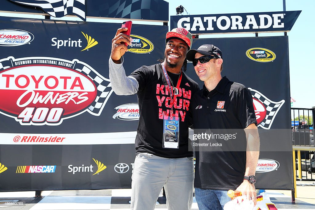 Robert Griffin III, of the Washington Redskins, takes a photo with Matt Kenseth, driver of the #20 Home Depot Husky Toyota, in victory lane prior to the NASCAR Sprint Cup Series Toyota Owners 400 at Richmond International Raceway on April 26, 2014 in Richmond, Virginia.