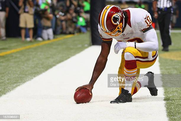 Robert Griffin III of the Washington Redskins 'Tebows' in celebration after scoring a touchdown against the St Louis Rams at the Edward Jones Dome on...