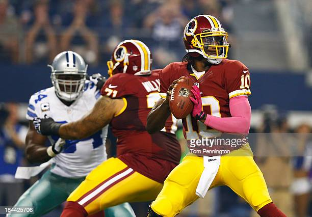 Robert Griffin III of the Washington Redskins throws a pass in the first quarter of a game against the Dallas Cowboys at ATT Stadium on October 13...
