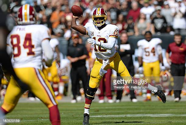 Robert Griffin III of the Washington Redskins throws a pass to Niles Paul during the first quarter against the Oakland Raiders at Oco Coliseum on...