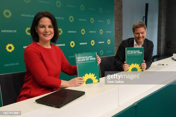 Robert Habeck and Annalene Baerbock, co-leaders of the German Greens Party, hold up a description of the party's policy program at a livestreamed,...