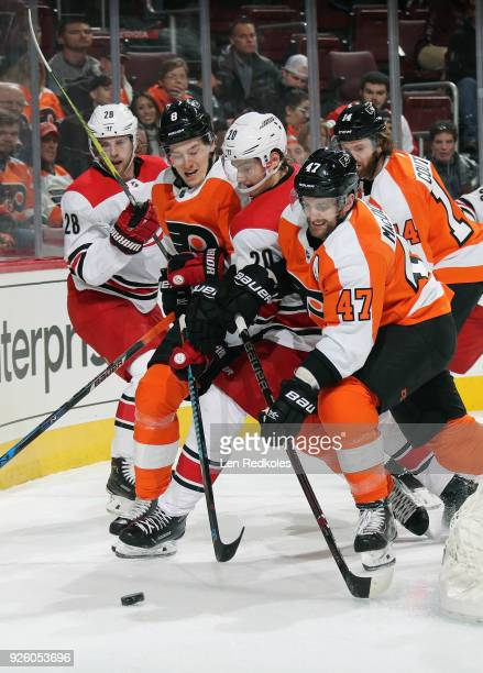 Robert Hagg and Andrew MacDonald of the Philadelphia Flyers battle for the loose puck behind the net with Elias Lindholm and Sebastian Aho of the...