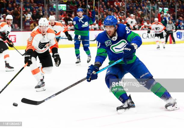 Robert Hagg of the Philadelphia Flyers and Brandon Sutter of the Vancouver Canucks reach for a loose puck during their NHL game at Rogers Arena...