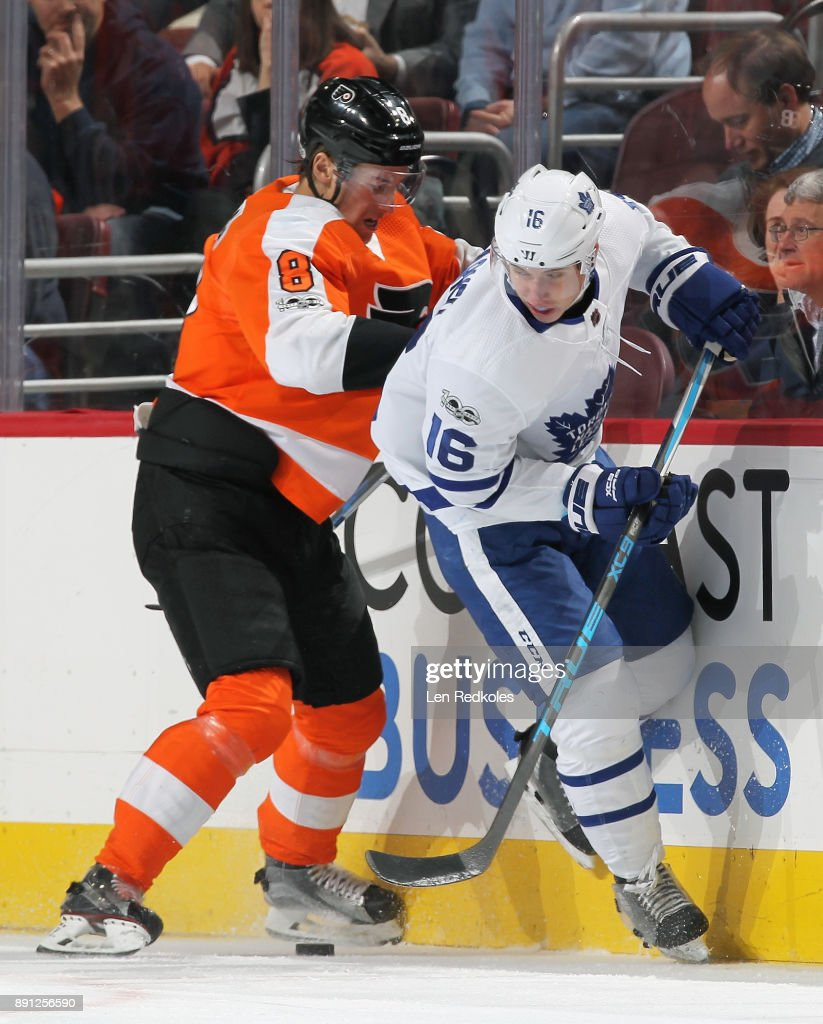 Robert Hagg #8 of the Philadelphia Flyers battles along the boards for the loose puck with Mitchell Marner #16 of the Toronto Maple Leafs on December 12, 2017 at the Wells Fargo Center in Philadelphia, Pennsylvania. The Flyers went on to defeat the Maple Leafs 4-2.