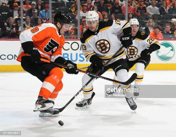 Robert Hagg of the Philadelphia Flyers reacts to the loose puck against Charlie Coyle and Ondrej Kase of the Boston Bruins on March 10 2020 at the...