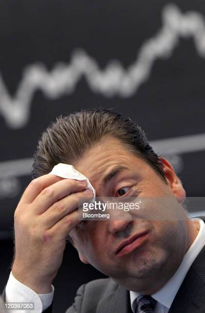 Robert Halver a financial trader wipes his forehead in front of the DAX Index curve at the Frankfurt Stock Exchange in Frankfurt Germany on Friday...