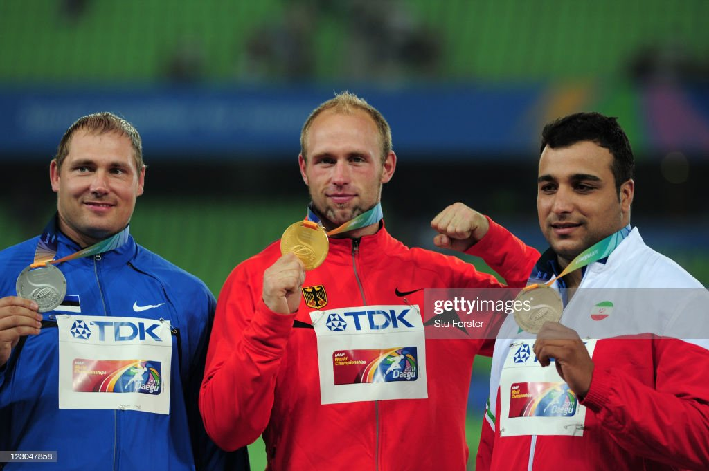 Robert Harting of Germany poses with the gold medal after his victory in the Men's discus final with Gerd Kanter of Estonia (L) and Ehsan Hadadi of Iran (R) during day four of the 13th IAAF World Athletics Championships at the Daegu Stadium on August 30, 2011 in Daegu, South Korea.