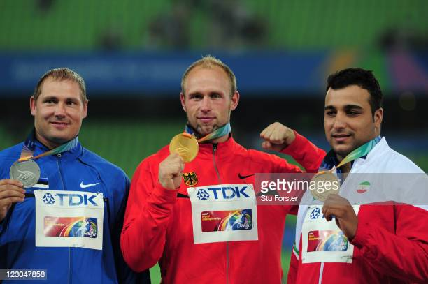 Robert Harting of Germany poses with the gold medal after his victory in the Men's discus final with Gerd Kanter of Estonia and Ehsan Hadadi of Iran...