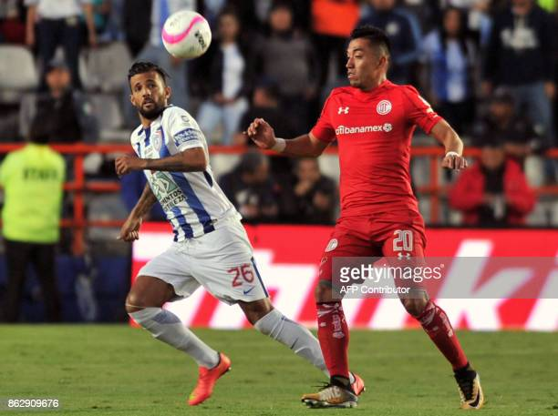 Robert Herrera of Pachuca vies for the ball with Fernando Uribe of Toluca during their Mexican Apertura tournament football match at the Hidalgo...