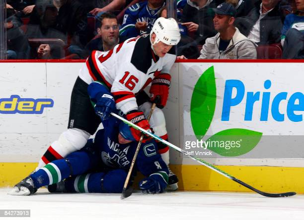 Robert Holik of the New Jersey Devils pins down Willie Mitchell of the Vancouver Canucks on the ice during their game at General Motors Place on...