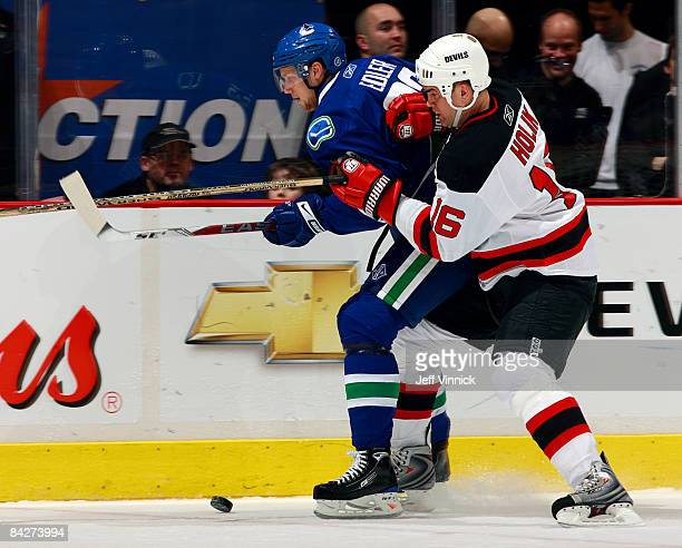 Robert Holik of the New Jersey Devils pushes Alexander Edler of the Vancouver Canucks along the boards during their game at General Motors Place on...