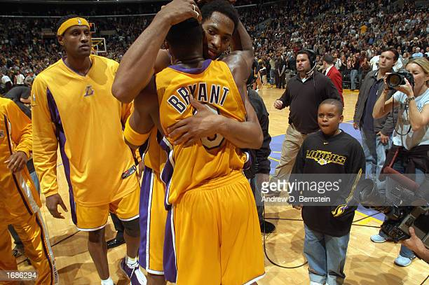 Robert Horry of the Los Angeles Lakers embraces Kobe Bryant as Samaki Walker look on as they celebrate the 30-point comeback win against the Dallas...