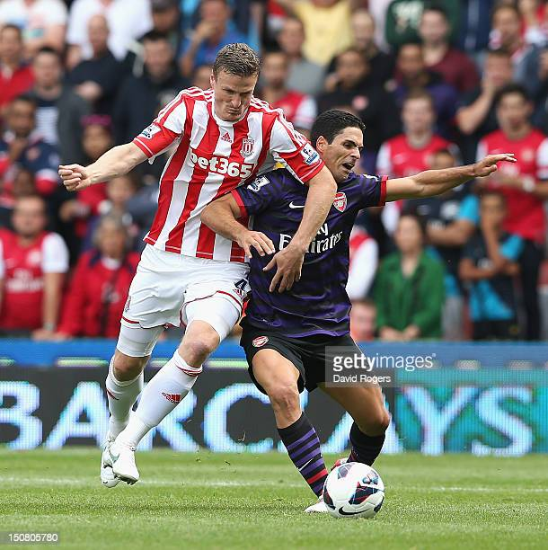 Robert Huth of Stoke City challenges MIkel Arteta during the Barclays Premier League match between Stoke City and Arsenal at the Britannia Stadium on...