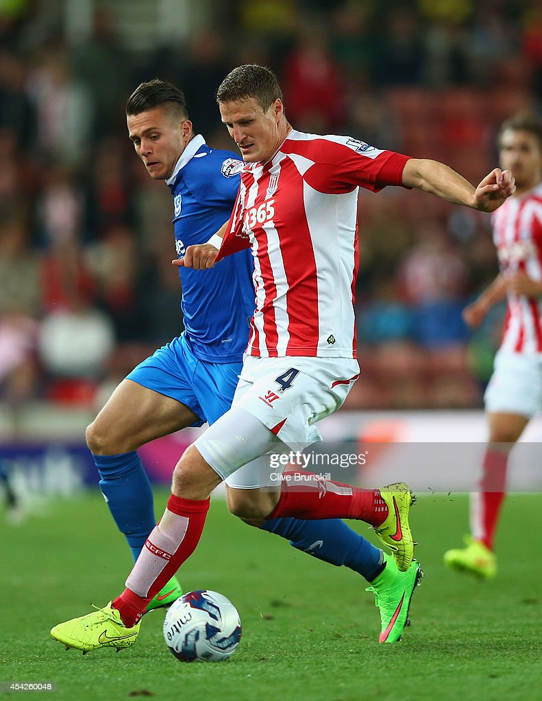 Robert Huth of Stoke City in action with Miles Storey of Portsmouth during the Capital One Cup Second Round match between Stoke City and Portsmouth at Britannia Stadium on August 27, 2014 in Stoke on Trent, England.