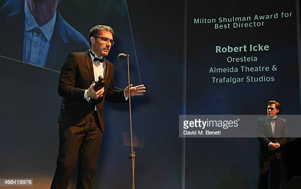 Robert Icke accepts the Best Director award for Oresteia as host Rob Brydon looks on at The London Evening Standard Theatre Awards in partnership...