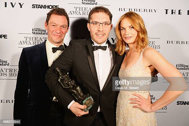 Robert Icke winner of Best Director for Oresteia poses with presenters Dominic West and Ruth Wilson in front of the Winners Boards at The London...