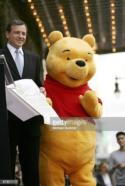 Robert Iger President and Chief Executive Officer The Walt Disney Company and Winnie The Pooh pose for photographs celebrating Winnie The Pooh's Star...