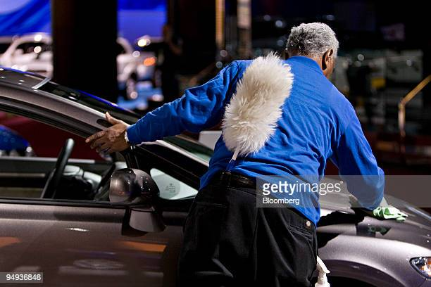 Robert Jackson of ABM Janitorial Services cleans cars in the Honda Motor Co booth at the 2009 North American International Auto Show in Detroit...
