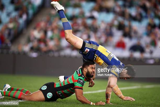 Robert Jennings of the Rabbitohs plays the ball under pressure from Tepai Moeroa of the Eels during the round 20 NRL match between the South Sydney...