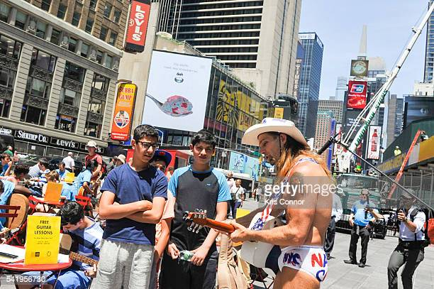 Robert John Burck aka The Naked Cowboy visits Make Music Day Guitar Lessons/Mass Appeal in Time Square on June 21 2016 in New York City