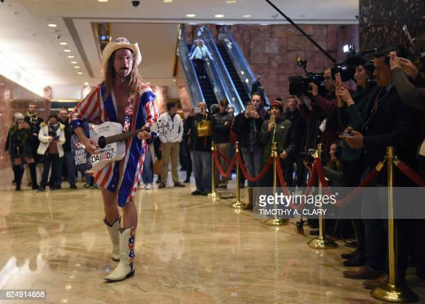 Robert John Burck better known as the 'Naked Cowboy' sings to the media at Trump Tower on another day of meetings for Presidentelect Donald Trump...