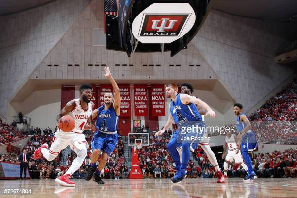 Robert Johnson of the Indiana Hoosiers drives to the basket against Brenton Scott and Bronson Kessinger of the Indiana State Sycamores in the first...