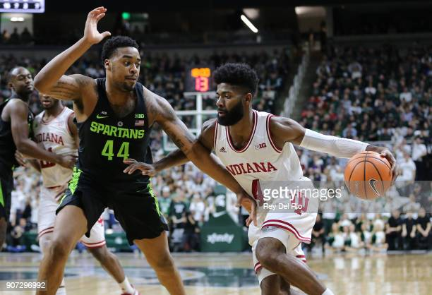 Robert Johnson of the Indiana Hoosiers drives to the basket while defended by Nick Ward of the Michigan State Spartansat Breslin Center on January 19...