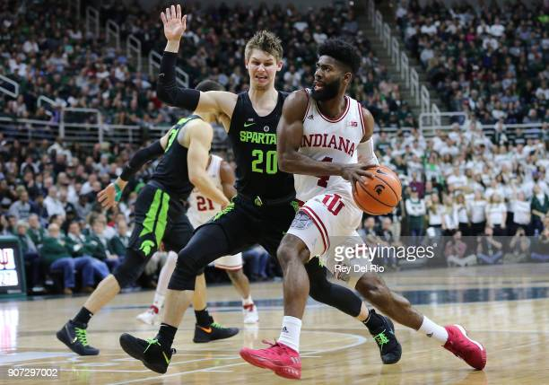 Robert Johnson of the Indiana Hoosiers drives to the basket while defended by Matt McQuaid of the Michigan State Spartans at Breslin Center on...