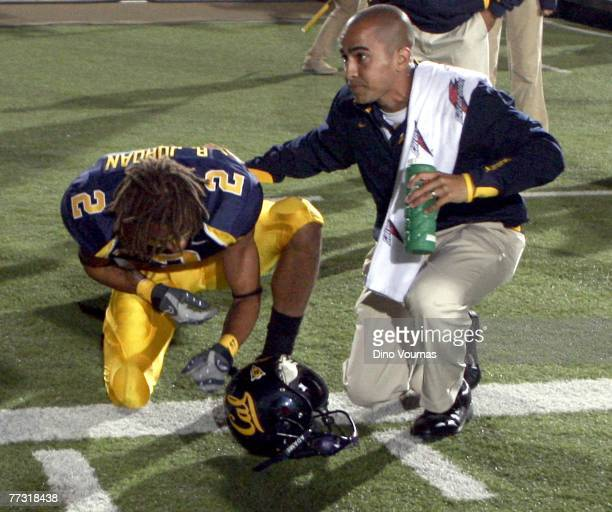 Robert Jordan of the California Golden Bears is comforted by an unidentified coach after the Oregon State Beavers beat them at Memorial Stadium on...