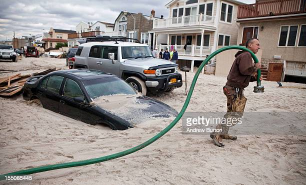 Robert Justh drags a hose while attempting to drain a flooded basement caused by Hurricane Sandy on October 31 2012 in Long Beach New YorkThe storm...