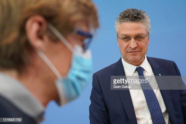 Robert Koch Institute President Lothar Wieler speaks to a journalist who is wearing a protective face mask following a press conference with other...