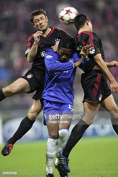 Robert Kovac and Lucio of Bayern Munich challenge in the air with Didier Drogba of Chelsea during the UEFA Champions League quarter final second leg...