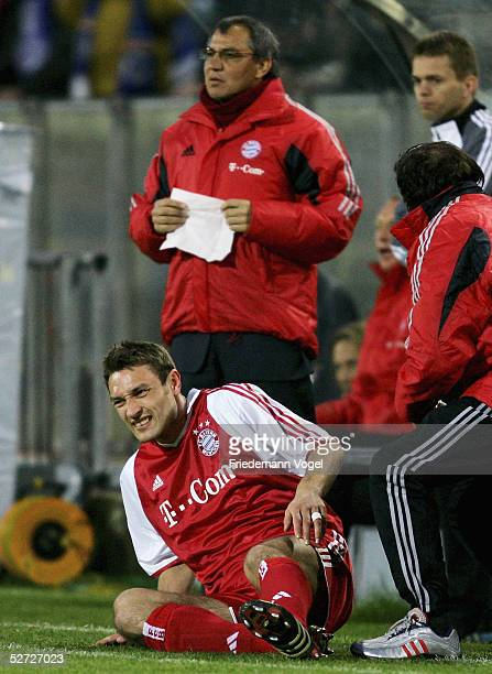 Robert Kovac of Bayern receives treatment as coach Felix Magath looks on in the background during the DFB Pokal Semi Final Match between Arminia...