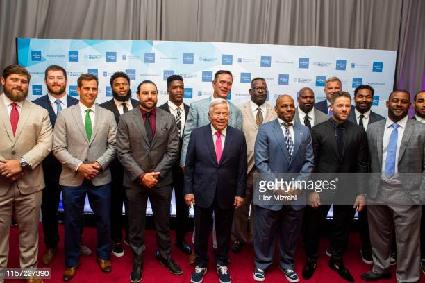 Robert Kraft surrounded pose with NFL players of Patriots team during the red carpet at the Genesis Prize at The Jerusalem Theater on June 20 2019 in...