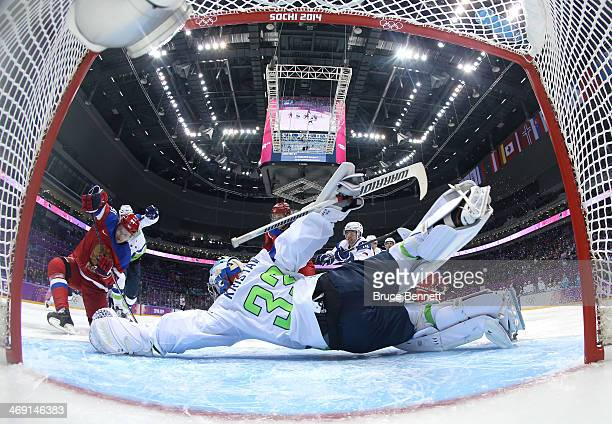 Robert Kristan of Slovenia dives to make a save against Vladimir Tarasenko of Russia in the first period during the Men's Ice Hockey Preliminary...