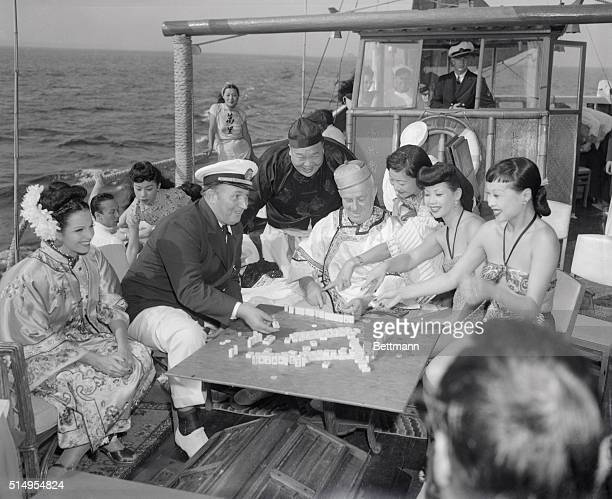 Robert L Believe It Or Not Ripley and his guests are shown aboard his colorful Chinese Junk the Mon Lei enjoying a game of Mah Jong before starting...