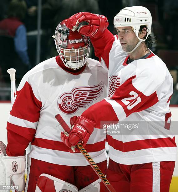 Robert Lang of the Detroit Red Wings congratulates teammate Dominik Hasek after defeating the Vancouver Canucks at General Motors Place on November...