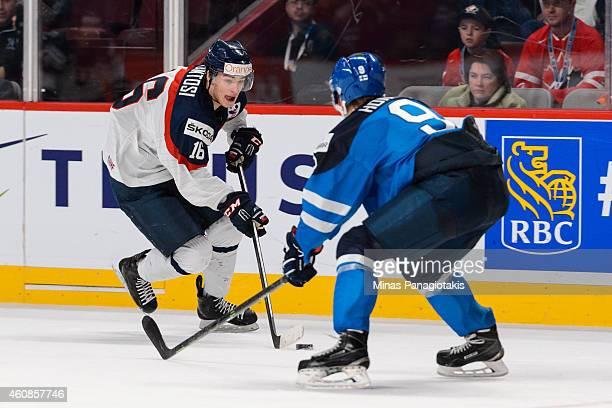 Robert Lantosi of Team Slovakia carries the puck near Julius Honka of Team Finland during the 2015 IIHF World Junior Hockey Championship game at the...