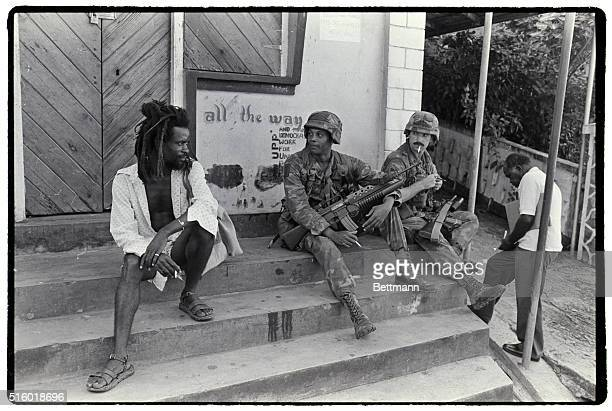 Robert Lawerence and a colleague patrolling the west coast of Grenada during the Grenada Invasion stop to chat with a local resident on the steps of...