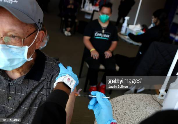 Robert Leong gets a COVID-19 vaccination with his son Ryan, a Special Olympics athlete, during a vaccination clinic for Special Olympics athletes,...