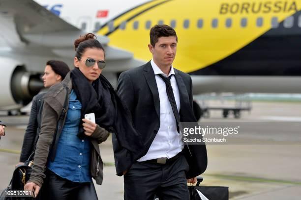 Robert Lewandowski and his fiance Anna Stachurska walk across the tarmac as the Borussia Dortmund return to Dortmund Airport after UEFA Champions...