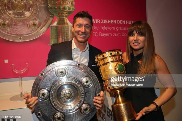 Robert Lewandowski and his wife Anna Lewandowska pose with the DFB Cup and Bundesliga Championship trophies during the FC Bayern Muenchen DFB Cup...
