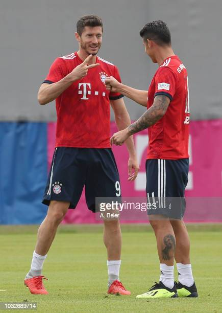Robert Lewandowski and James Rodriguez of FC Bayern Muenchen joke during a training session at the club's Saebener Strasse training ground on...
