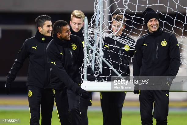 Robert Lewandowski and Marian Sarr of Dortmund carry a goal with team mates during a training session ahead of the UEFA Champions League Round of 16...