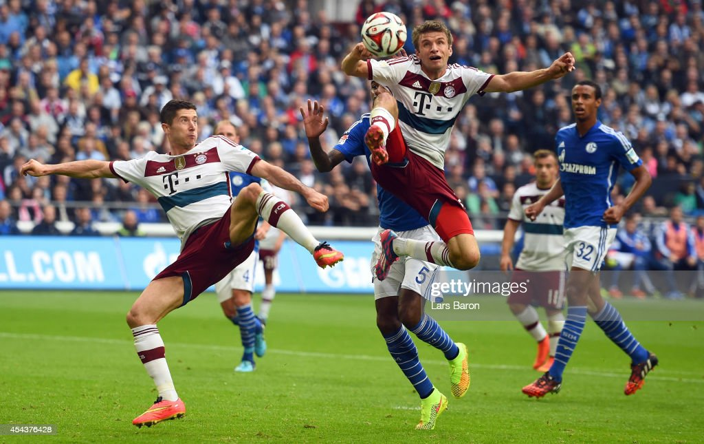 Robert Lewandowski and Thomas Mueller of Muenchen jump for the ball during the Bundesliga match between FC Schalke 04 and FC Bayern Muenchen at Veltins Arena on August 30, 2014 in Gelsenkirchen, Germany.