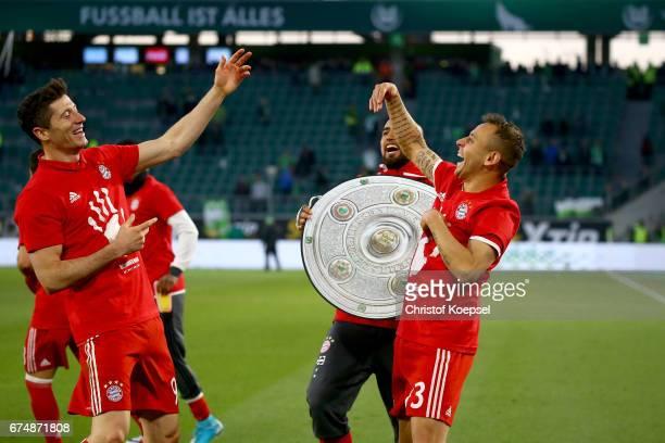 Robert Lewandowski, Arturo Vidal and Rafinha of Bayern celebrate after winning the German Championship after winning 6-0 the Bundesliga match between...