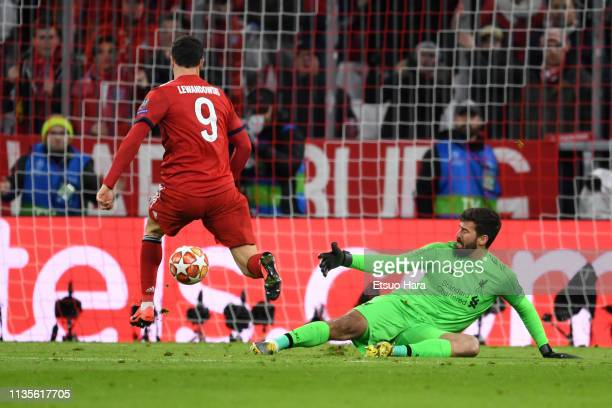Robert Lewandowski of Bayern Muenchen and Alisson Becker of Liverpool compete for the ball during the UEFA Champions League Round of 16 Second Leg...