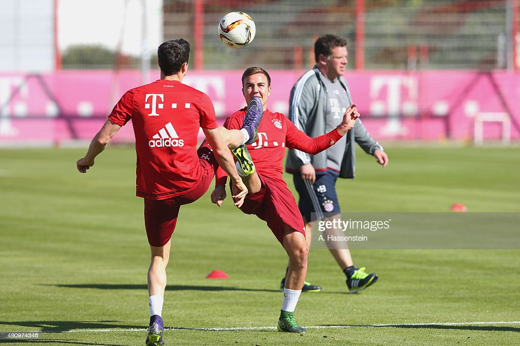 Robert Lewandowski (L) of Bayern Muenchen battles for the ball with his team mate Mario Goetze during a training session at Bayern Muenchen's trainings ground Saebener Strasse on October 2, 2015 in Munich, Germany.