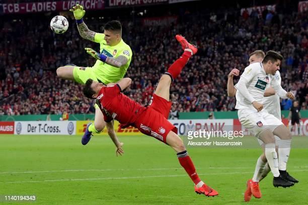 Robert Lewandowski of Bayern Muenchen battles for the ball with Kevin Mueller keeper of Heidenheim during the DFB Cup match between FC Bayern...